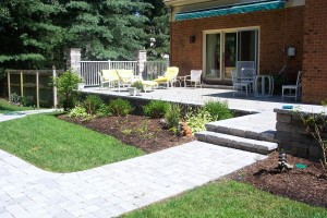 This is a raised patio that transitions down to a walkway with nice landscaping.